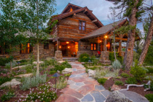 Photo of timber framed home with rock pathways and garden beds
