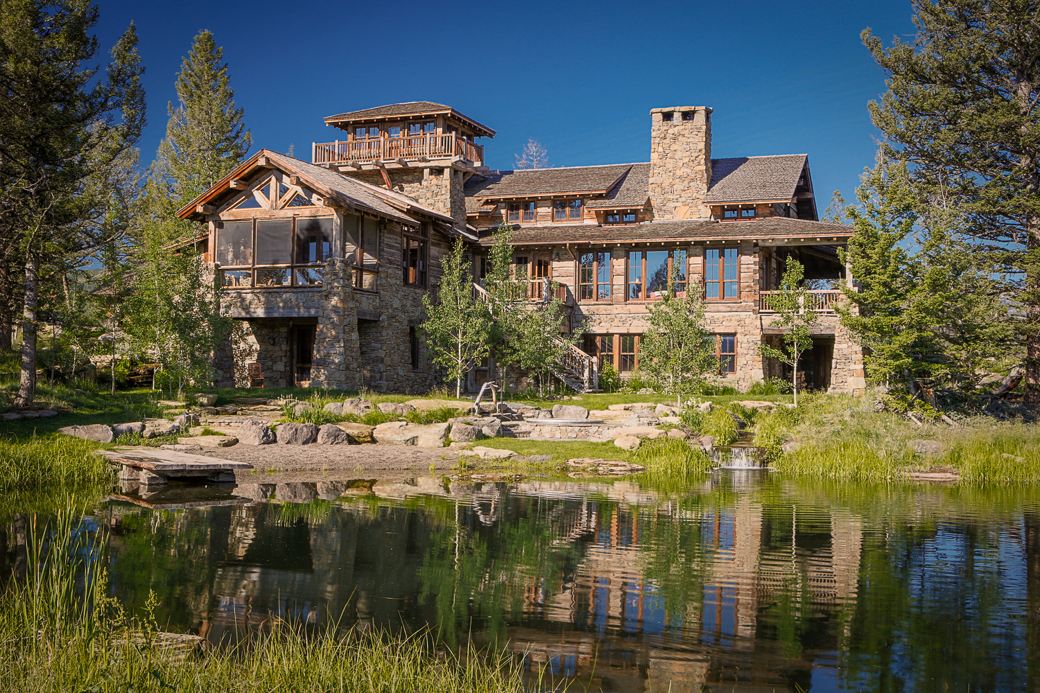 Photo of large stone house with pond